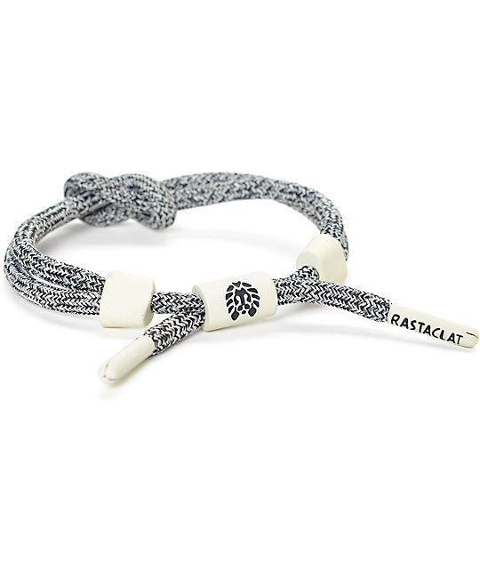 The Wolfy Knotclat bracelet from Rastaclat features a salt and pepper grey fabric construction with a knot in the center and is finished with metal Rastaclat hardware and slider to adjust to your wrist for a personalized fit.