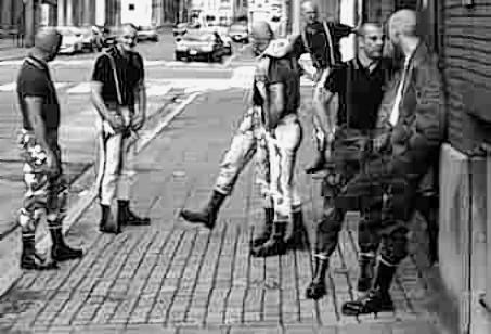 British skinheads in the seventies. The skinhead thing came out of the mod youth movement - the boots were meant as a proud working class signifier. The original skinheads listened to ska reggae and northern soul. Much later the movement came to be associated with far right and nazi politics. Nowadays the only people you see dressed this way are bizarrely gay blokes, probably because it's a very macho look, and maybe the occasional aging original skin, hanging at the back in reggae clubs.