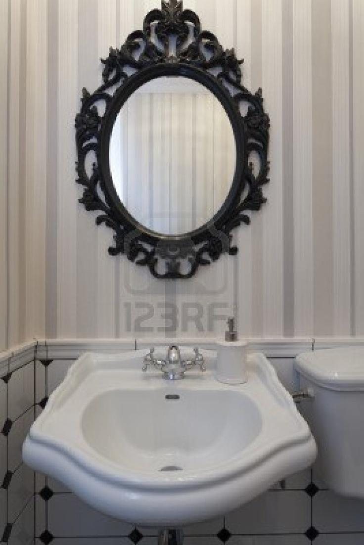 Elegante lavandino bianco e specchio ovale in toilette Archivio Fotografico