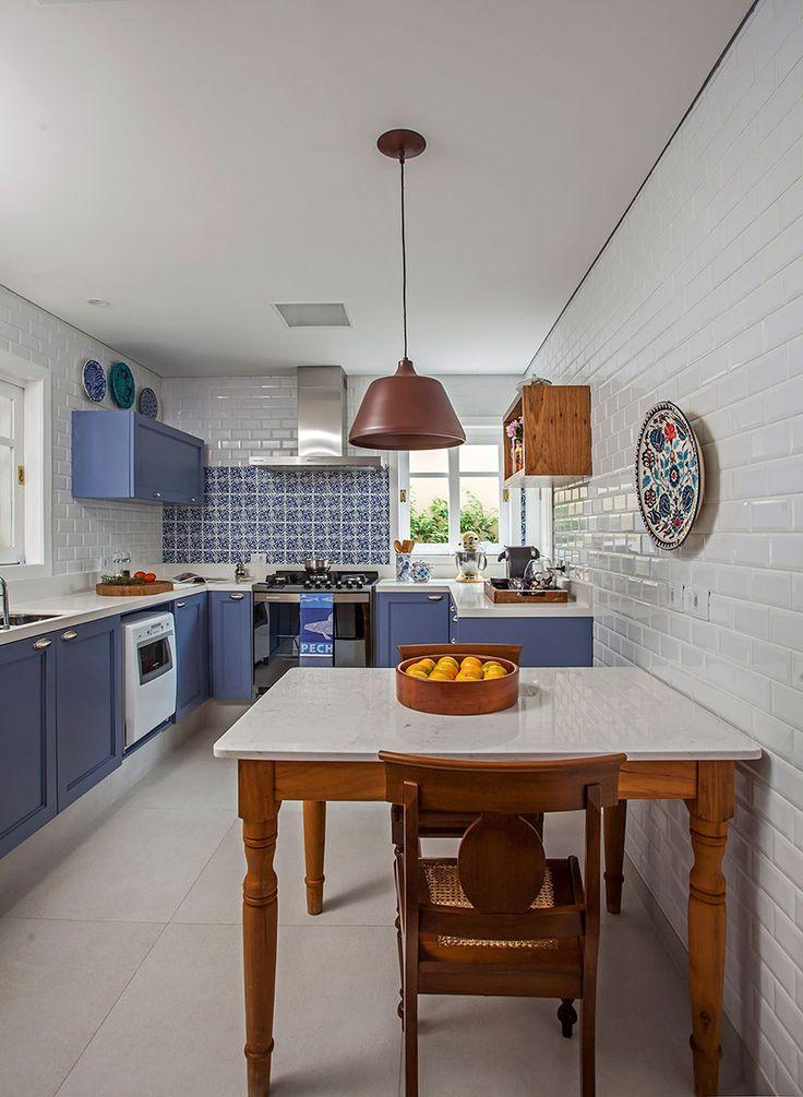 Decoração de casa com móveis antigos e contemporâneos. Na cozinha, parede de tijolinho branco, armário azul, mesa de jantar de madeira, cadeira de madeira e pendente.
