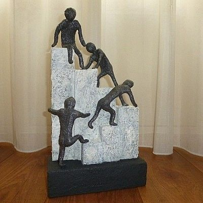 Abstract beeld of figuur beeld van vier figuren die samen tegen de pilaren omhoog klimmen. Een Kunst beeld dat als woonaccessoire passend is in bijna elk interieur of woninginrichting.