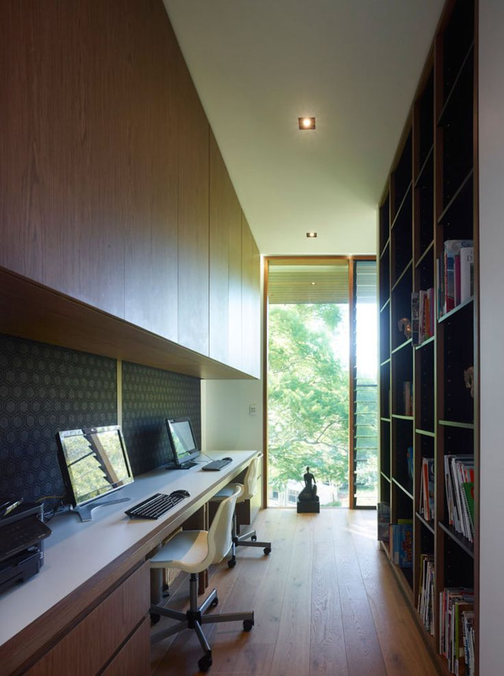 This home office has a built-in desk with cabinetry and a bookshelf. A window at the end of the room lets lots of natural light in.