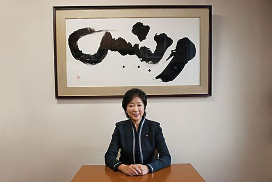 "Yuriko Koike, who has served as Japan's minister of environment from 2004 to 2006 & defense in 2007 sits in her office with her own abstract calligraphic rendering of the Arabic word shams (""sun"") splashed on a large framed canvas behind her. Beautiful work!"