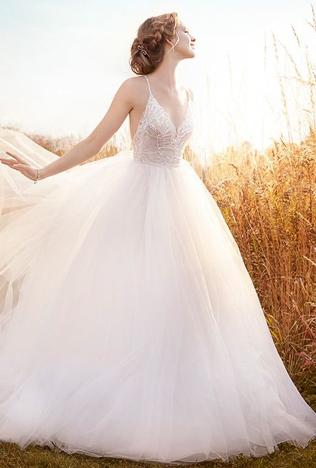 Ivory tulle ball gown with a sheer sequin embroidered bodice. V-neckline, natural waist, open back and sweep train.