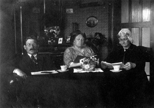 Gezinstaferelen. Familie J. Vegten aan tafel, de oude moeder met kanten muts met oorijzers (klederdracht). Ter Apel, Nederland,  2 februari 1924.