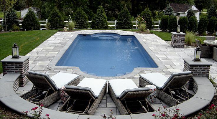 Formal shape fiberglass pool with brick and bluestone columns and seat wall