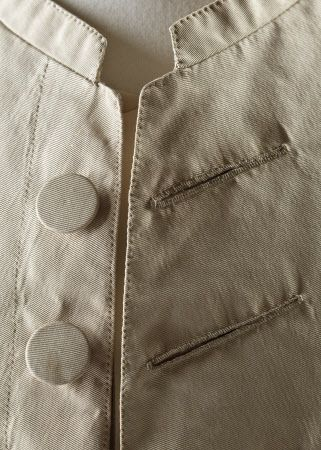 Detail of jacket buttons and buttonholes of a man's cream silk wedding suit, 18th century, part of the costume collection at Ham House, Surrey.