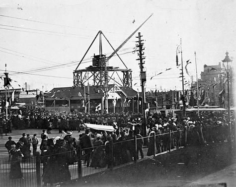 Construction of Flinders Street Railway Station. There is a large crane on a platform in the background. There are large crowds lining Swanston Street and bunting on poles.