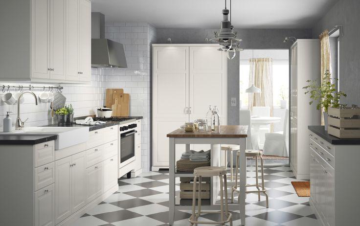 Cucina in bianco sporco con piani di lavoro neri e maniglie e pomelli cromati. Cappa in acciaio inossidabile e cucina beige – IKEA