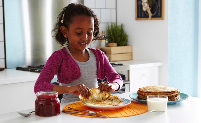 Young girl placing a pancake on a plate in front of her