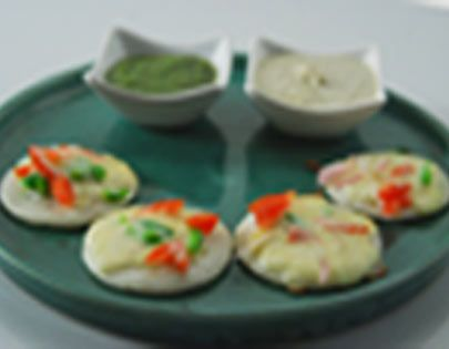 Small uttapams topped with onion, tomato, green capsicum and mozzarella cheese.