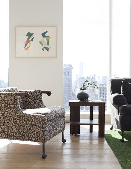 A simple, wood side table flanked by armchairs in a New York City apartment