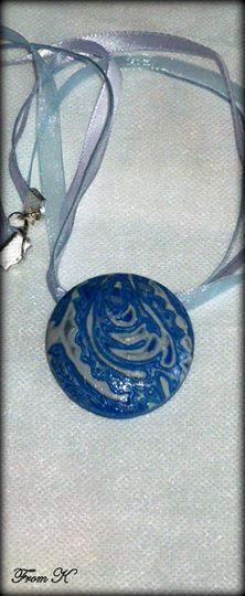 Blue Paisley Round Pendant. This unique necklace made with polymer clay, using the Hidden Magic technique. Clay was conditioned, layered, imprinted with a paisley design and finally carved of the top layer to reveal the beautiful result. have been sanded, buffed and sealed for a silky smooth finish. One of a kind necklace for people who aren't afraid to stand out from the crowd. About 4 cm in diameter. Finished with 41cm long ribbon and cotton cord with a lobster claw clasp. 20.00 Ron