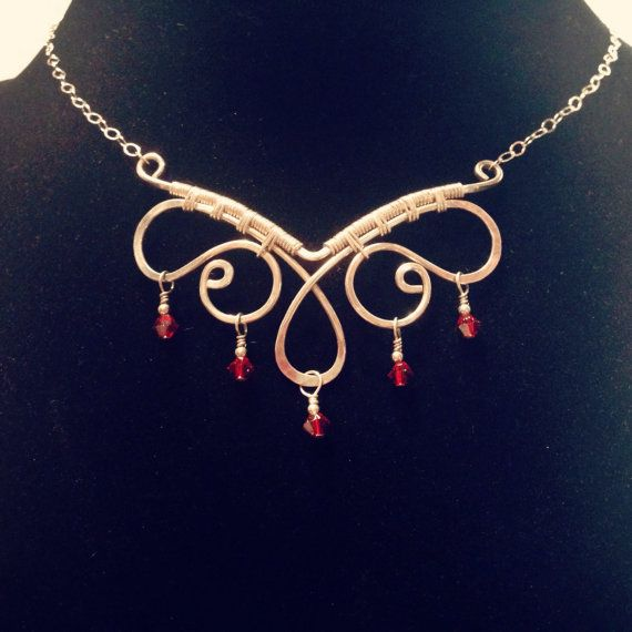 This necklace was formed using 16 gauge Sterling Silver wire wrapped with 24 gauge wire, and accented with 4mm red Swarovski crystal beads. The perfect gift for all occasions