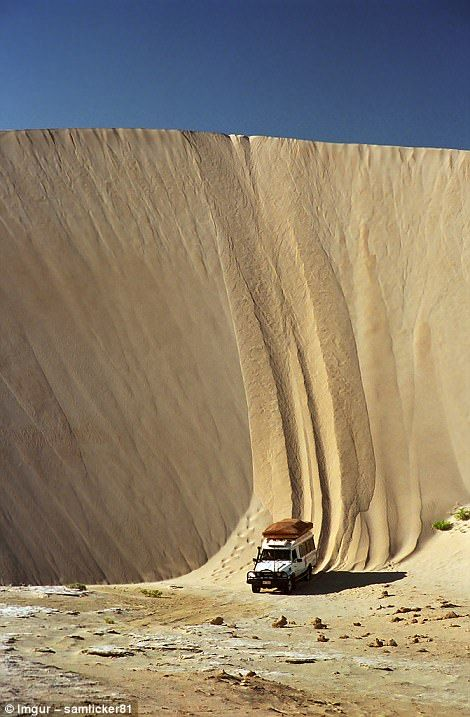 A 4X4 hurtles down a sand dune in Lucky Bay, Australia...