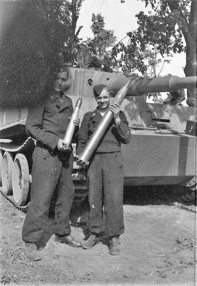 The crew of aTiger 1 show off the 88mm amunition used by their tanks powerful gun!