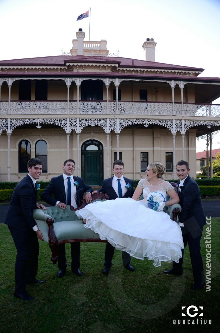 Groom and three groomsmen lifting the bride up on an old fancy lounge chair, in front of the mansion at Woodlands of Marburg. #WeddingPhotography