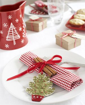 Pretty gingham checked napkins and homespun decorations give the Christmas table a welcoming rustic feel. Use a strong coloured ribbon, and either home-sewn or felt decorations to continue the country theme.: