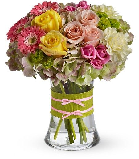 "This arrangement would be perfect for any girl with an eye for style. It's a must-have for fashionistas everywhere. Gorgeous  hydrangea, yellow and light pink roses, pink spray roses and mini gerberas, light yellow carnations and green button spray chrysanthemums are delivered in a pretty 6"" tall gathering vase. Not just any vase, of course, this one's accessorized with a chartreuse  and pink ribbon. Approximately 10"" W x 11"" H. Fashionista Blooms 