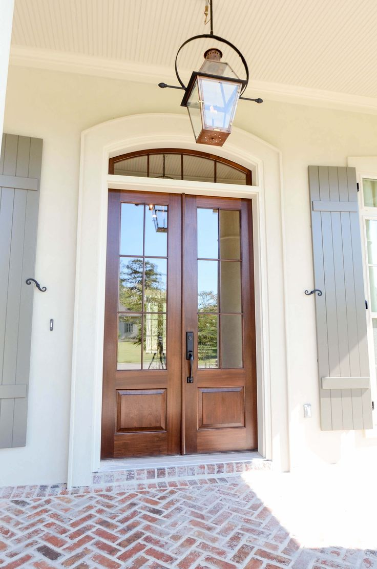 Entry with arched French style doors, a lantern from Bevolo in New Orleans, and Herringbone Brick
