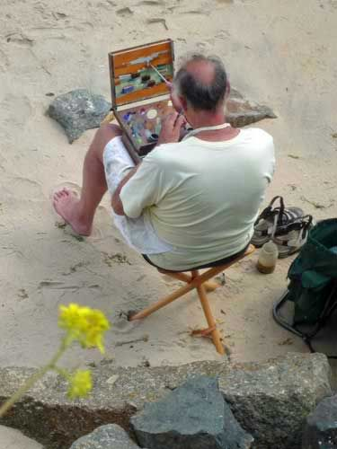 St Ives artist Eric Ward painting in Mousehole harbour