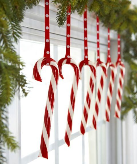 Hooked onto polka-dot ribbons, a row of candy canes livens up a bough-decked window.