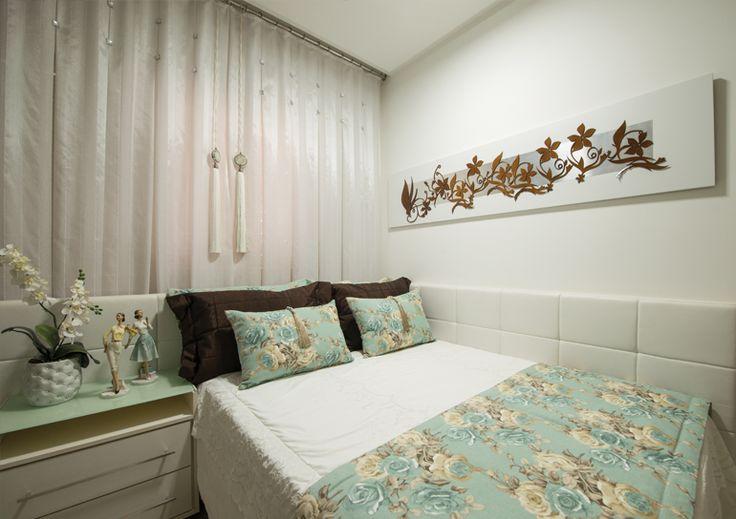 """Esse dormitório é destinado às visitas. Por isso, recebeu uma composição """"mais alegre"""", com base nas cores branca e azul. Para melhor aproveitamento do espaço, a cama foi encostada na parede, sendo emoldurada pelo painel revestido em couro branco que se estende além da cabeceira."""