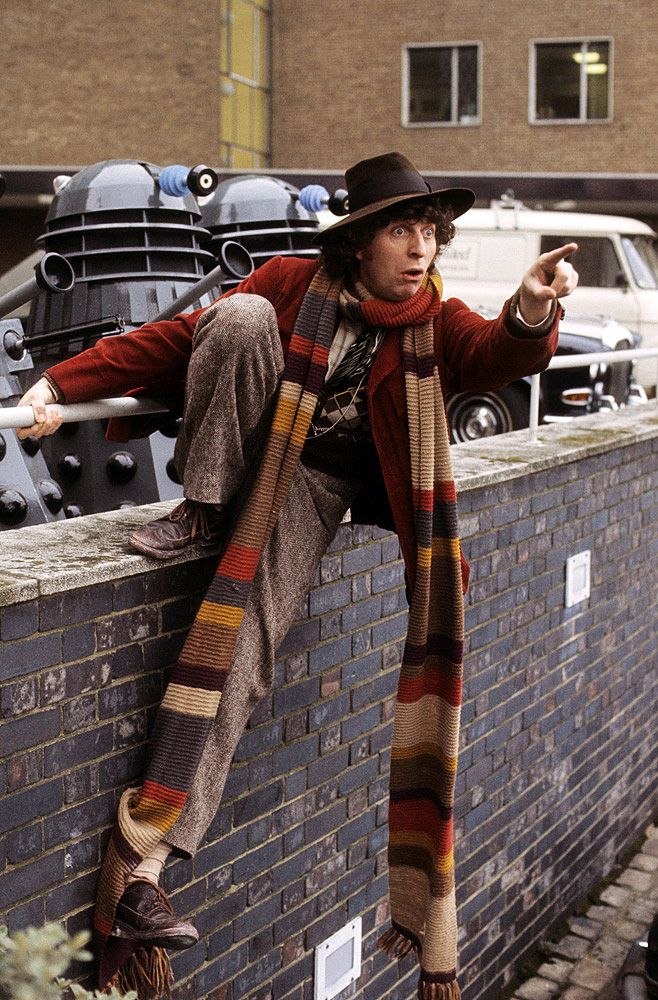 """When Tom Baker was cast as the Doctor, costume designer James Acheson picked up a load of wool and asked a knitter called Begonia Pope to knit a scarf for Tom. She inadvertently used all the wool Acheson had given her, resulting in a scarf that was some twenty feet long. This unusual scarf was well received by the cast and crew and after being shortened slightly, it was worn by Baker beginning on """"Robot."""""""
