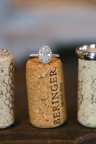 21 Creative Engagement Ring Photo Ideas: Oval-cut diamond engagement ring with halo and thin band displayed on wine cork {Megan Vaughan Photography}