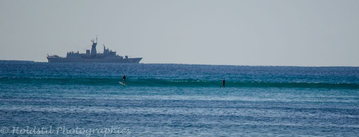 Nikon D5100 Auto mode no flash. 1/2000 sec exposure f/5.6 Focal Length 300mm Lens 55-300mm ISO auto (400). I noticed these guys on their boards as a war ship passed. Looks like they are paddling out to it