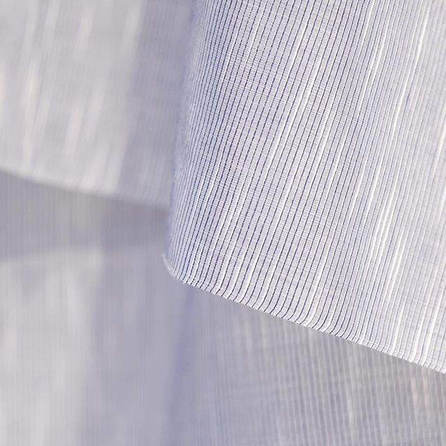 A plain blue surface with white highlights. The essence of the FLAME curtain is that shimmering light effect, coming from a combination of a structured white cotton yarn and a worsted wool yarn.