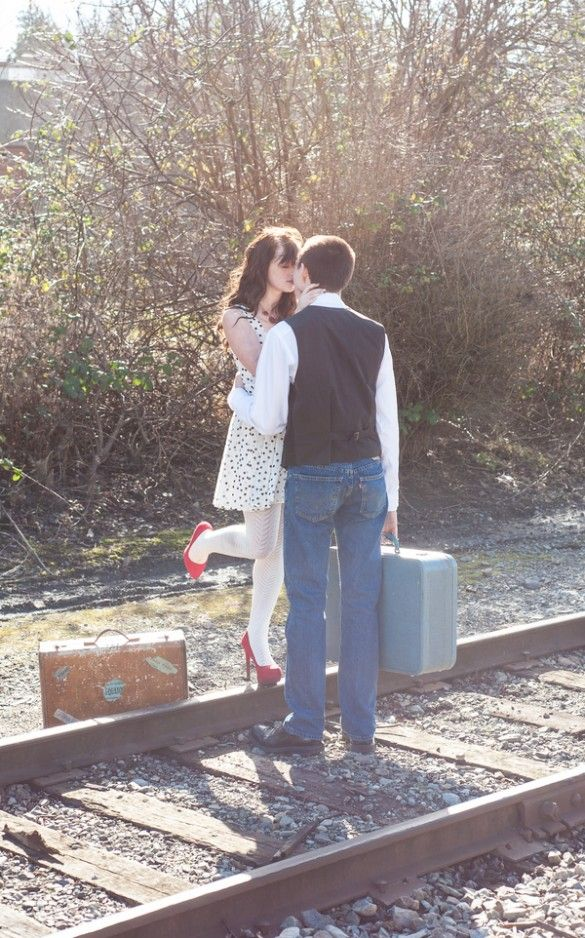 Vintage engagement photography session with old suitcases, polka dot dress and red heels on railway tracks by B. Jones Photography