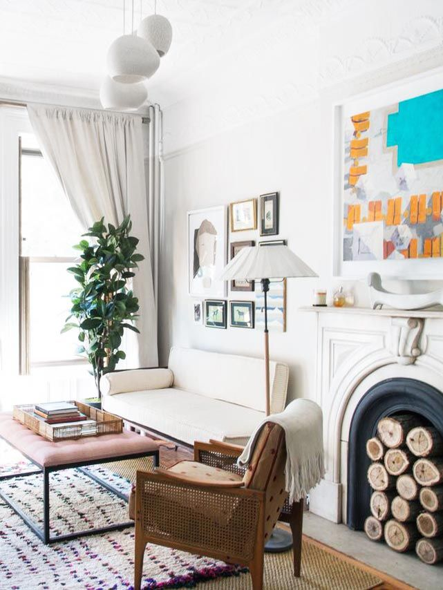 Eclectic bedroom sitting area with gallery wall and stacked logs in the fireplace on Thou Swell @thouswellblog