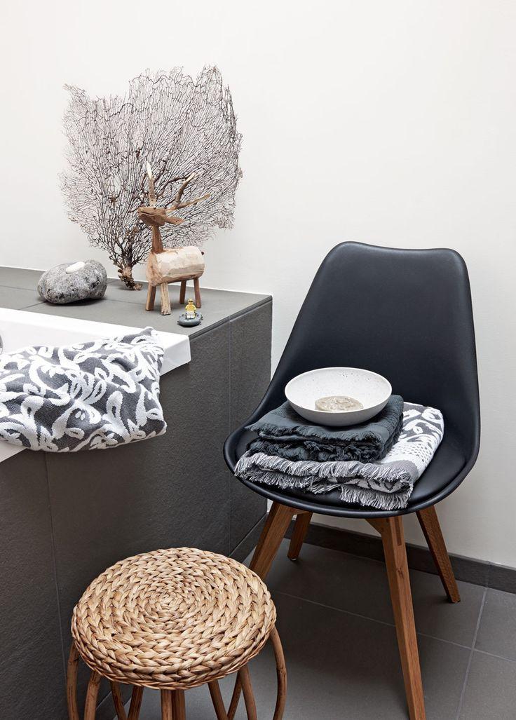 Natuurlijke materialen in de badkamer in contrast met stoere zwarte/donkergrijze accenten.