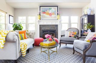 Gorgeous living room. More formal, neutral furniture, matched with lots of fun pops of color. Love the greys, along with the grey undertones in the beige wall color. Great patterned area rug, and airy coffee table.