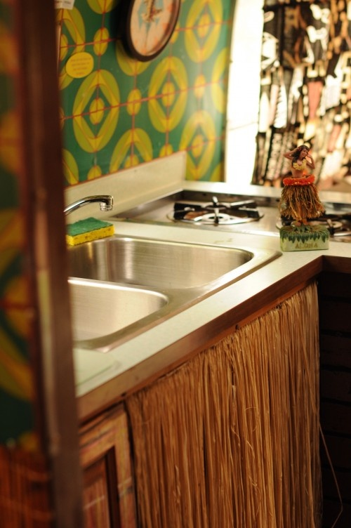 """The geometric, flashy wallpaper in the airstream's kitchen complemented the Tiki-style straw curtain below the sink."""