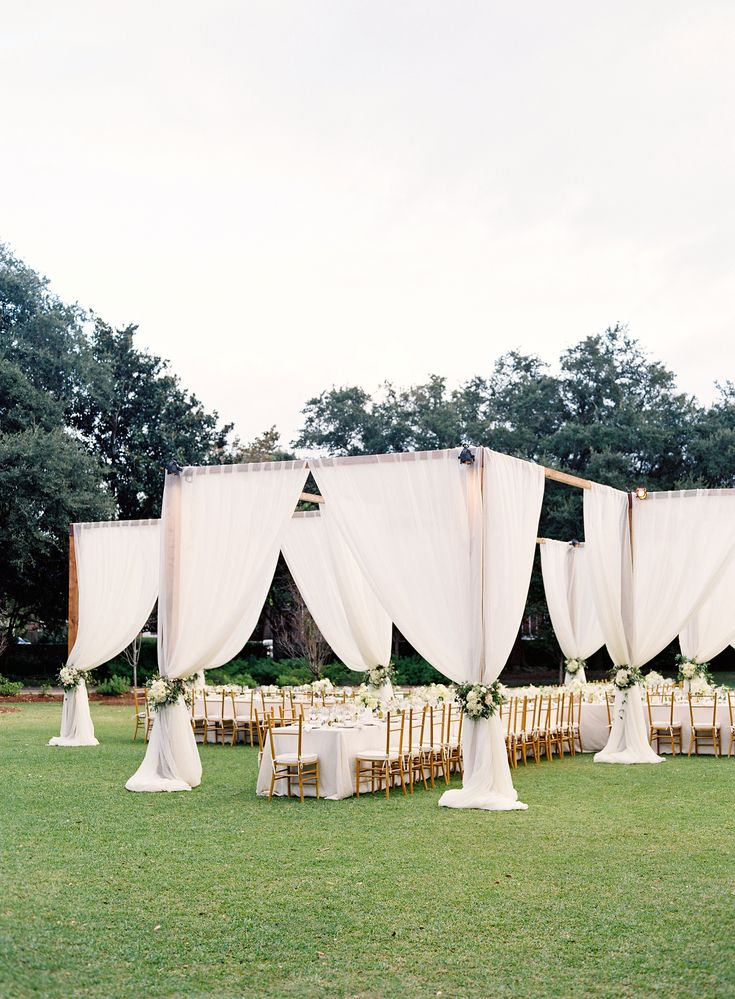 Open-air dining in x-shape, floral tie-backs at Easton Events Charleston wedding.