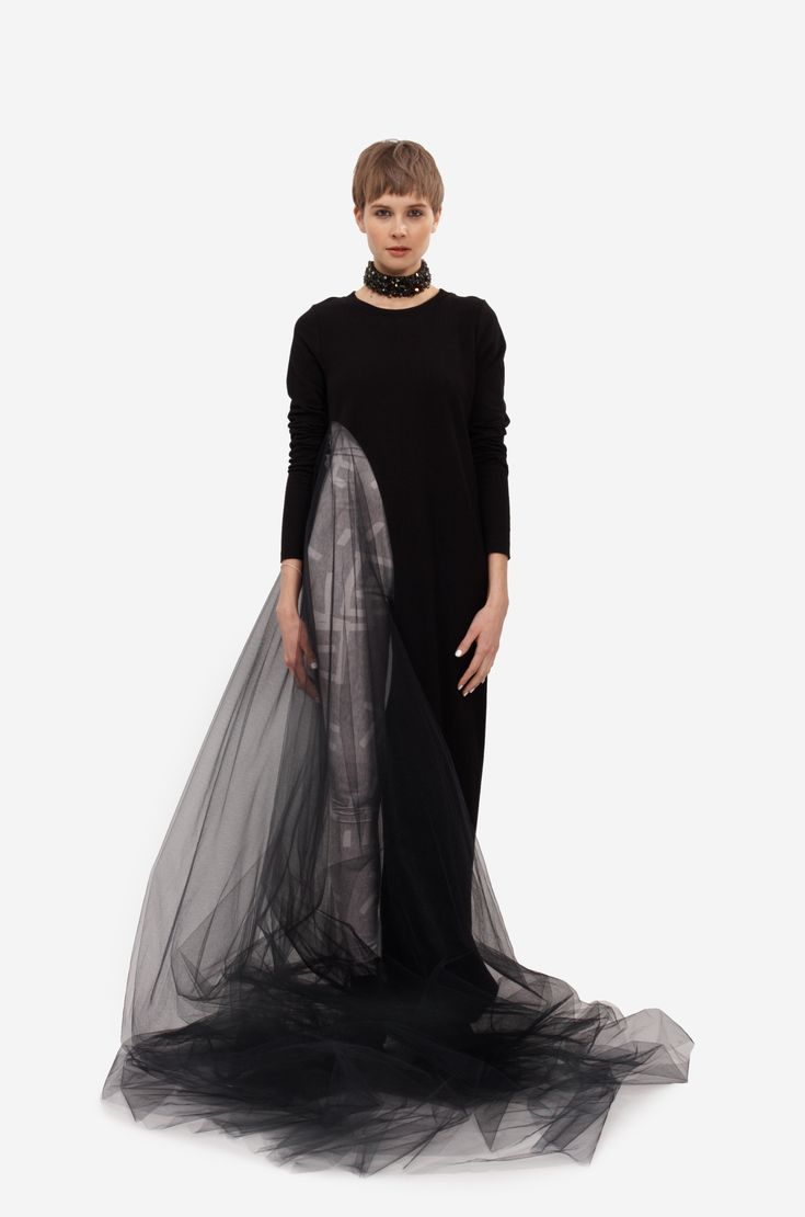 """MAXI DRESS """"SIDE WIND"""" Shorthaired model wearing a black Maxi Dress """"Side Wind"""" with long sleeves and semitransparent prolonged part on side made of tulle. Under the dress model is wearing a smooth elastic overall with original grey print."""