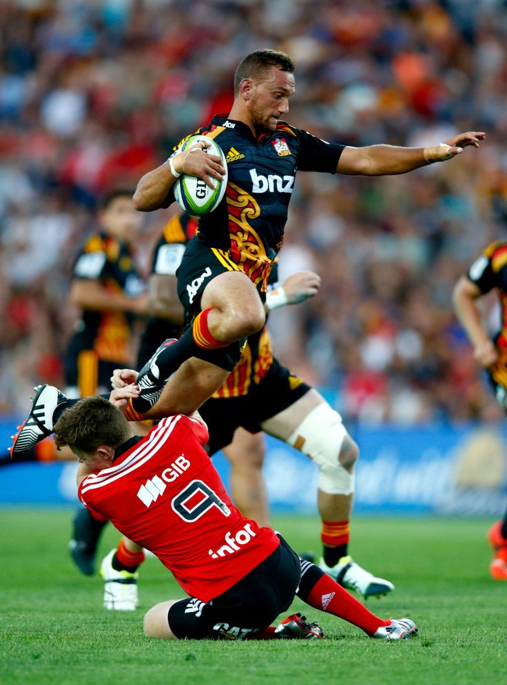 Aaron Cruden of the Chiefs leaps over the tackle of Mitchell Drummond of the Crusaders