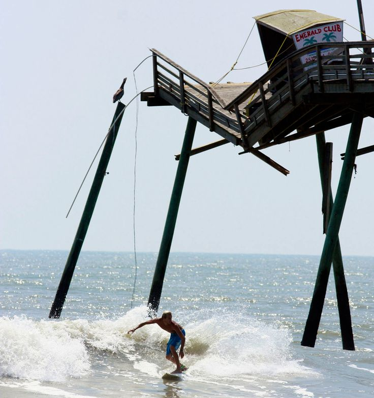 Hurricane Irene, 2011.  A surfer passes the broken end of the Bogue Inlet Fishing Pier in Emerald Isle, N.C. on August 28, 2011. Hurricane Irene spent 12 hours scouring the coast, killed at least five people, brought pockets of flooding that required rescues along the sounds, and left nearly a half-million customers without power. (John Rottet/The News & Observer/AP)