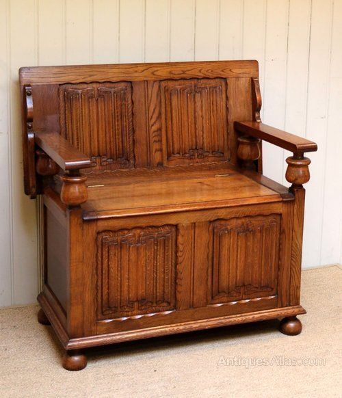 Solid oak monks bench having linenfold panelled front and back with turned wooden supports raised on bun feet.The top folds down to become a table which stands 79.5cm high
