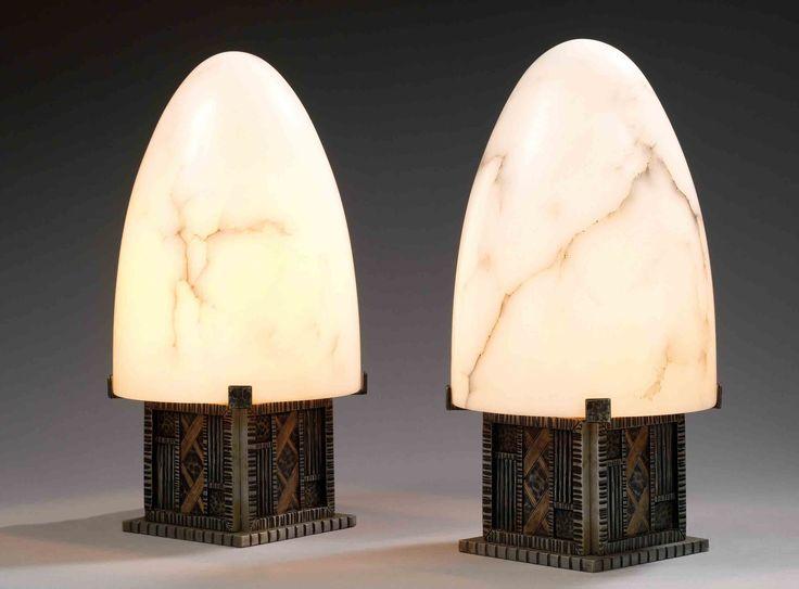 Michel Zadounaïsky (1903-1983)spectaculaire paire de lampes à poser, structure cubique en fer forgé, présentant sur une terrasse godronnée, des parements verticaux ornés en bas-relief de diverses plages travaillées à chaud, godrons, filets et martelage, patine noire, rehauts or, platine supérieure à quatre pattes de fixation, accueillant de grands dômes d'albâtre en forme d'ogives. (refaits postérieurement à l'identique). signature d'un cachet en creux. haut. 43,5 cm - diam. 22 cm