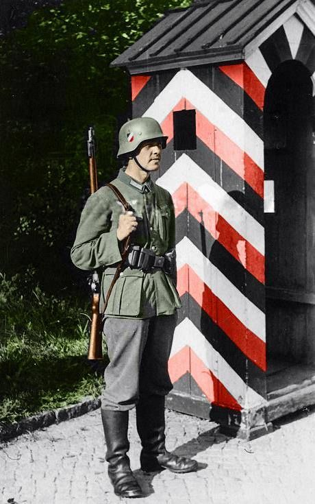 German Wehrmacht infantryman stands guard at a military checkpoint. Such installations were spread widely throughout the occupied lands in order to deter saboteurs and partisans from wreaking havoc. Most citizens living under the occupation of the Reich were required to surrender their personal details to the Reich administrative offices, whom then would initiate extensive background checks to ensure you don't pose a threat to German forces. If the check clears without points of contention…