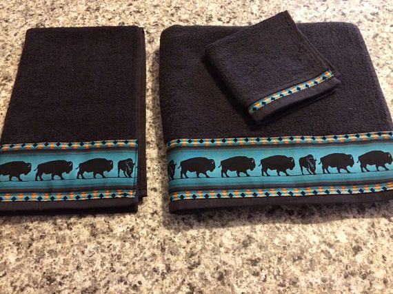 Set of three (3) bathroom towels includes one (1) bath towel, one (1) hand towel and one (1) face cloth. Medium thick good quality towels with a cotton western trim, gorgeous for a western housewarming gift. Black towels with teal bison and navajo edging. A very sharp looking classy  Southwestern. Buffalo. Bison.
