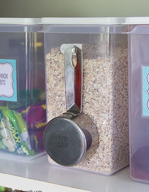 Store your dry goods in plastic containers and use a command hook to keep a scoop attached to the container.