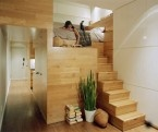 Stairs and the bed is mostly enclosed.