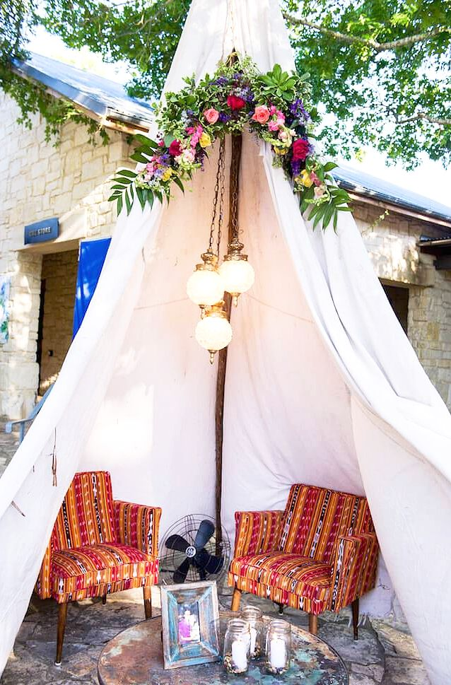 20 Epic Backyard Lighting Ideas to Inspire your Patio Makeover | DIY Outdoor Design Inspiration | Boho tent with pendants + floral arrangement—great wedding lounge idea!