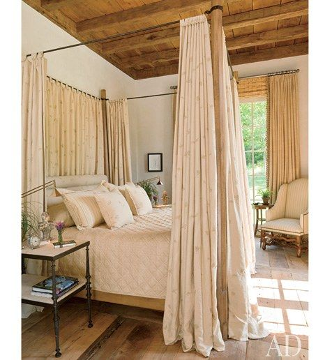 A Chelsea Editions fabric curtains a Formations four-poster in the master bedroom | archdigest.com