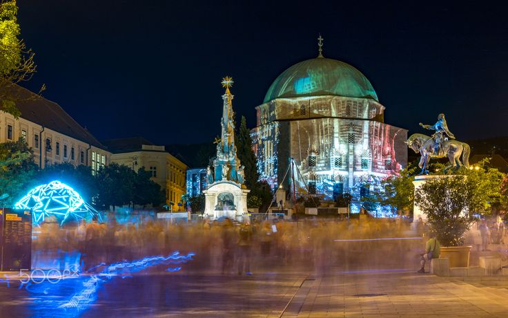 The way of the light - Light painting on the mosque with lights and crowd on the Széchenyi Square of Pécs, Baranya, Hungary. It was a part of the Zsolnay Light Festival. You can see also the Trinity, the Turkish mosque (changed to a catholic church now), the statue of king János Hunyadi and a high school. Long exposure photo, 90 sec.