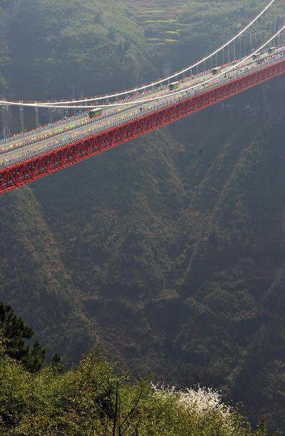 Los vehículos se desplazan en el lapso de tiempo Aizhai puente colgante en Xiangxi Tujia y Miao Prefectura Autónoma, Provincia de Hunan, centro de China, 31 de marzo de 2012. Aizhai puente colgante, con un vano principal de 1.176 metros y una altura máxima de 330 metros, fue abierta a el tráfico del sábado.  Que abarca más del cañón Dehang, el puente fue construido como parte de la autopista desde el suroeste de China Chongqing de la ciudad de Changsha, Hunan.  Su terminación mejoraría en…